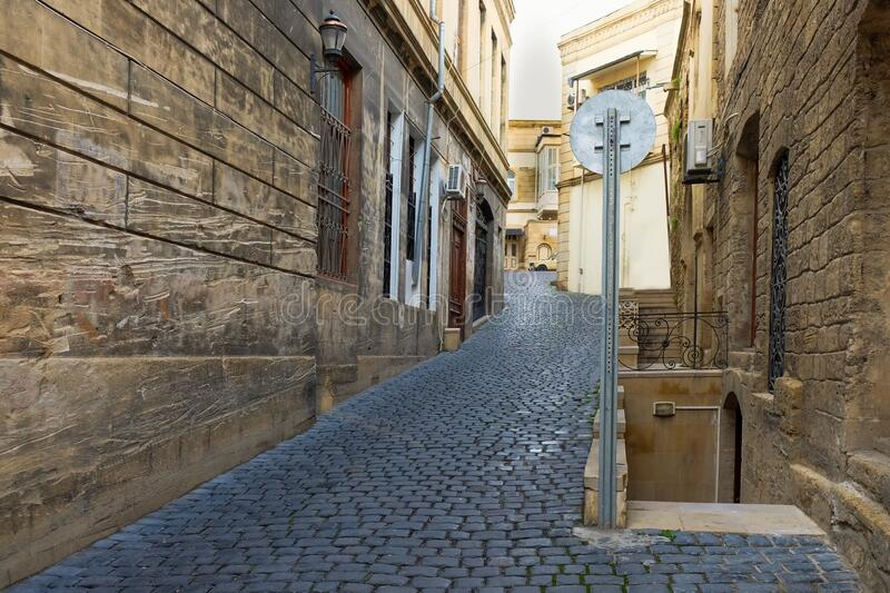 Perspective view to empty ascending narrow small street with traditional old black cobblestones pavement royalty free stock photography