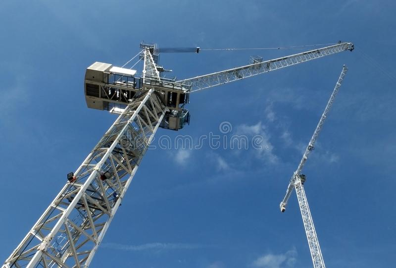 A perspective view of two tall white construction cranes on a building site against a blue sky with clouds stock images