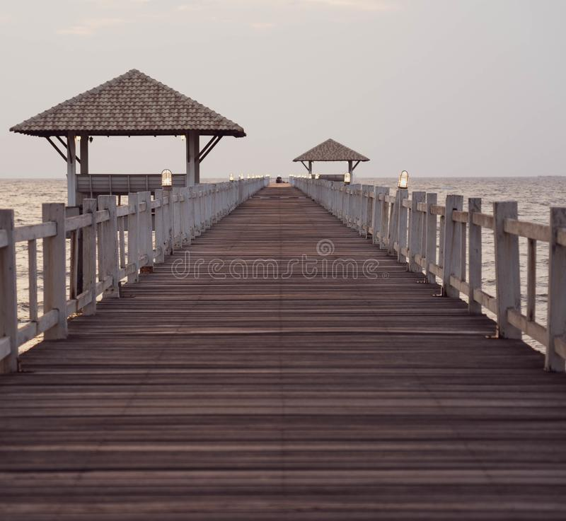 Perspective view of wooden bridge extending into the sea stock photo