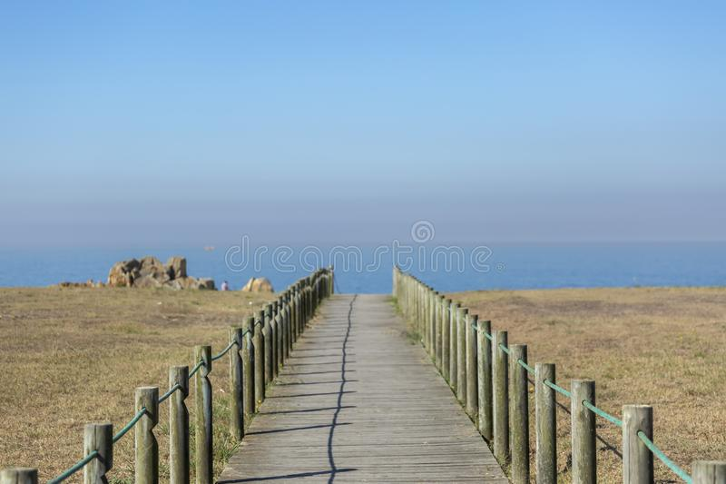 Perspective view of wooden pedestrian walkway, towards the ocean, next to the beach stock image