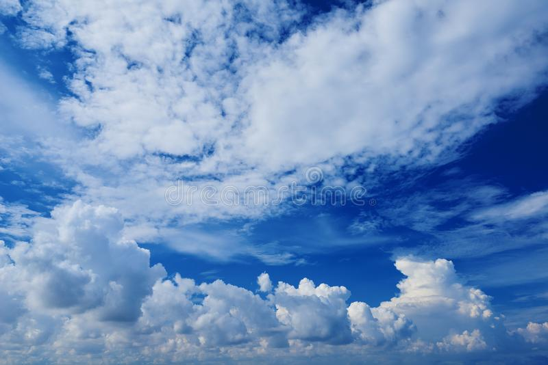 Perspective wide view of romantic navy blue sky with white grey clouds. High resolution artistic skyline background image royalty free stock image