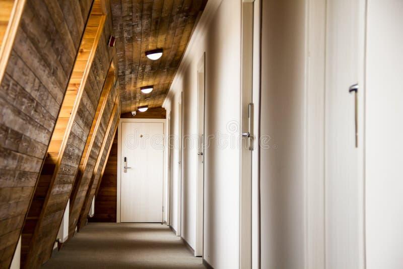 Perspektiv av en korridor med träväggar i ett hotell eller en dorm royaltyfri foto