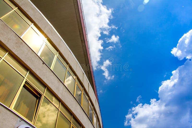 Perspektiv- och undersidavinkelsikt till texturerad bakgrund av modern exponeringsglasbyggnad över blå himmel fotografering för bildbyråer