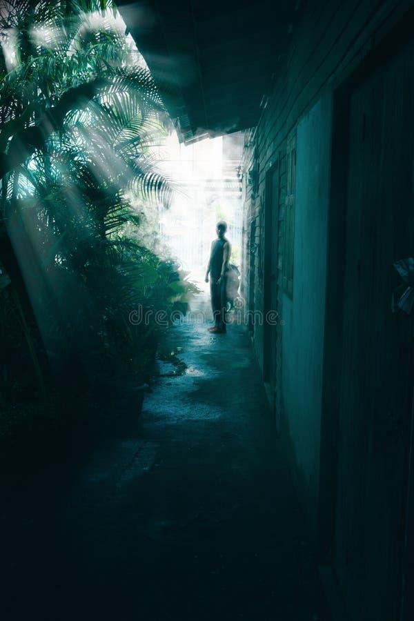 Perspektive des Mannes am Ende der Weise in der Dunkelheit mit Retro- verlassenem Haus lizenzfreies stockbild