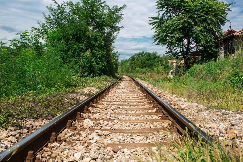 Perspektiven-Ansicht der Wege der alten Eisenbahn in den grünen Vorderteilen lizenzfreie stockfotografie