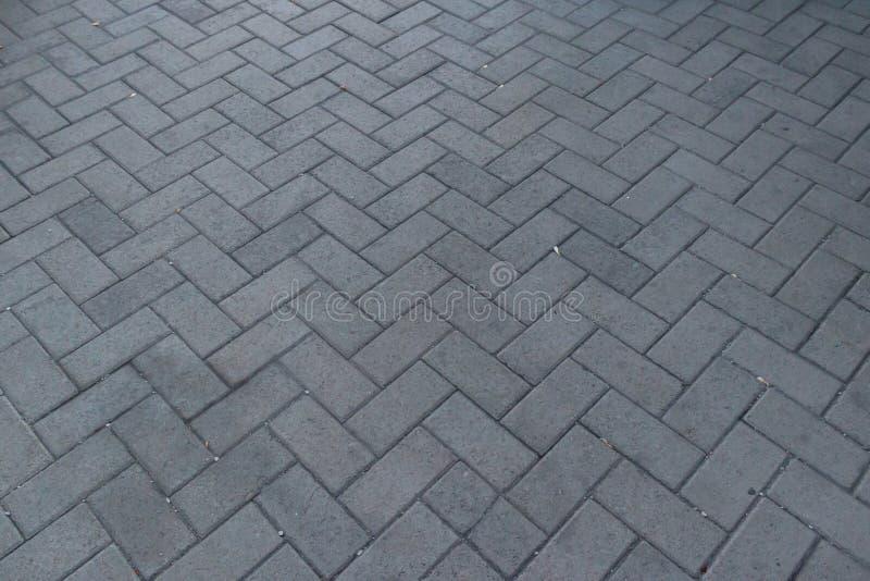 Perspektiven-Ansicht monotoner Gray Brick Stone Pavement aus den Grund für Straßen-Straße Bürgersteig, Fahrstraße, Straßenbetonie stockfotografie