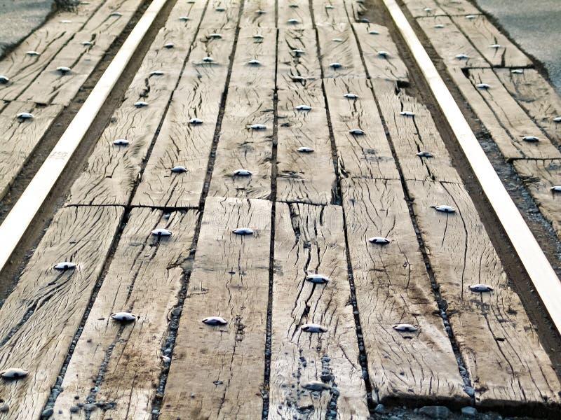 Perspektivenansicht der Eisenbahn spürt Straßenüberfahrt mit altem Holz und Bolzen - selektiver Fokus auf lizenzfreie stockbilder