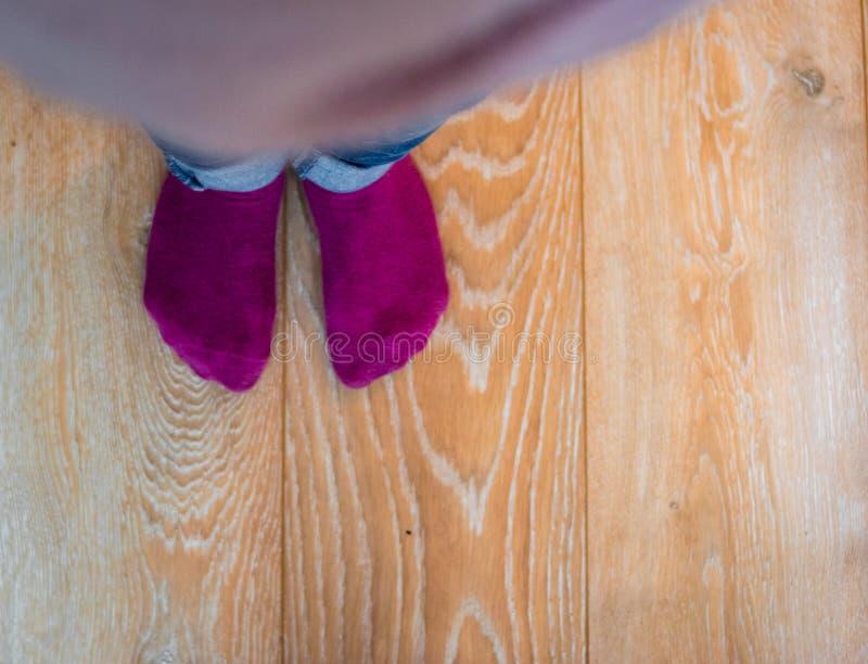 Perspektivenansicht von ein Kind-` s Füßen mit purpurroten Socken stockbild
