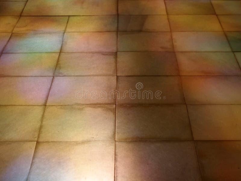 Perspektivsikt av ett belagt med tegel golv för gammal brun sten med färgade ljus- och solljusreflexioner på yttersidan royaltyfria foton
