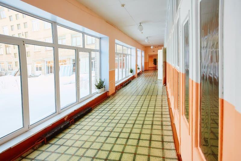 Perspektivsikt av gammal en skola- eller kontorsbyggnadkorridor, tom smalt, högt och långt, med många rumdörrar och Windows royaltyfri bild