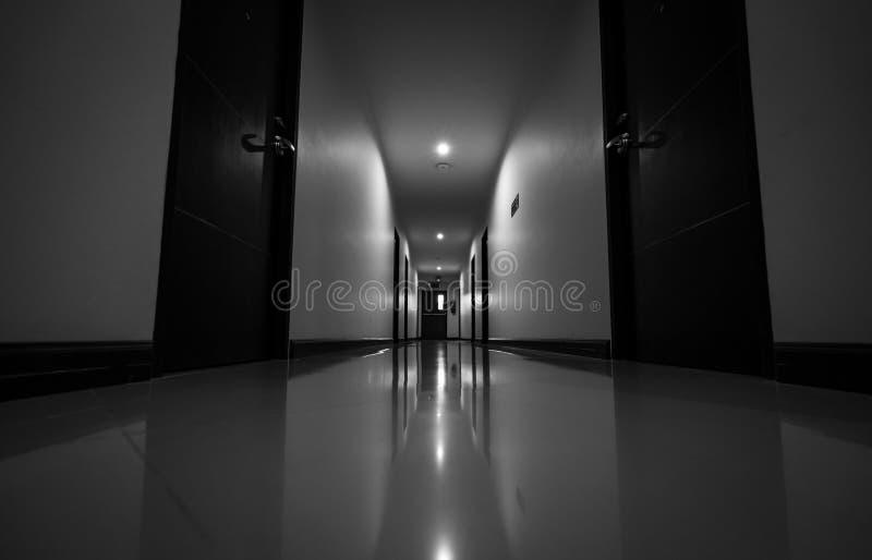 Perspektivsikt av hotellkorridoren med taklampljus Hall- och hotelldörr Tom passage till utgången för brandflykt inre royaltyfri fotografi