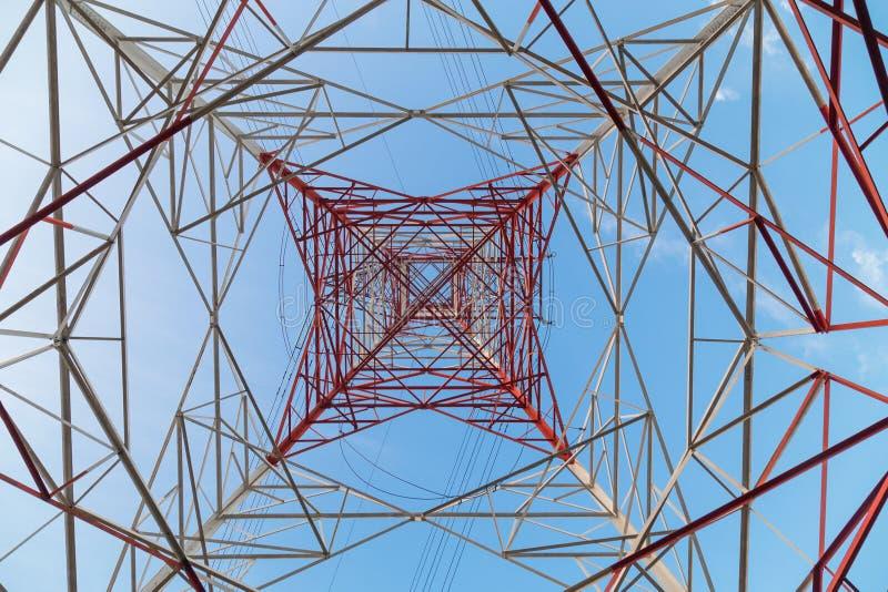 Perspektivsikt under en enorm röd pylon för elektricitetstillförsel arkivbild