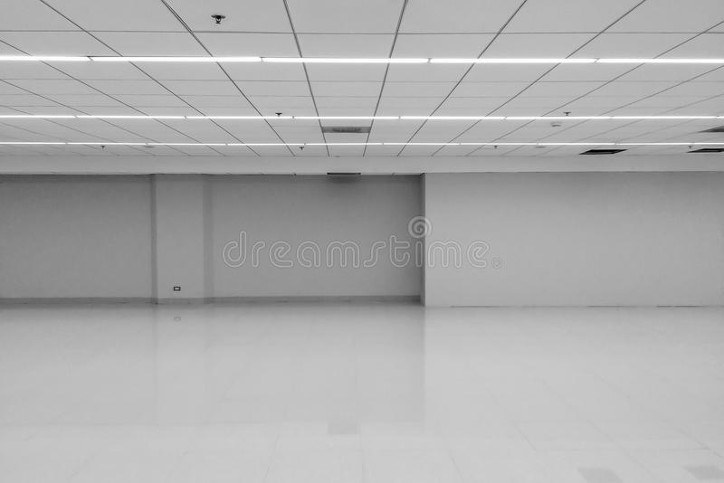 Perspektivsikten av rum för kontoret för tom klassisk entonighetsvart för utrymme vitt med radtaket LEDDE ljusa lampor och tänder arkivbild