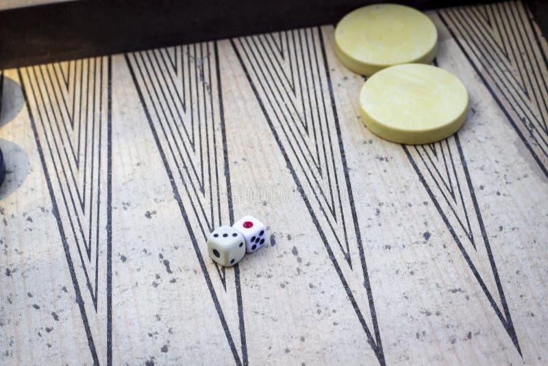 Perspektywiczny krótkopęd dices na trik-trak pod otwartym światłem z sztuka kamieniami obraz royalty free