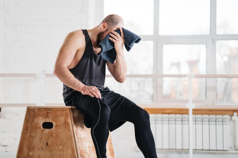 Perspiring fit sportsman resting after work session cross workout in light hall stock photo