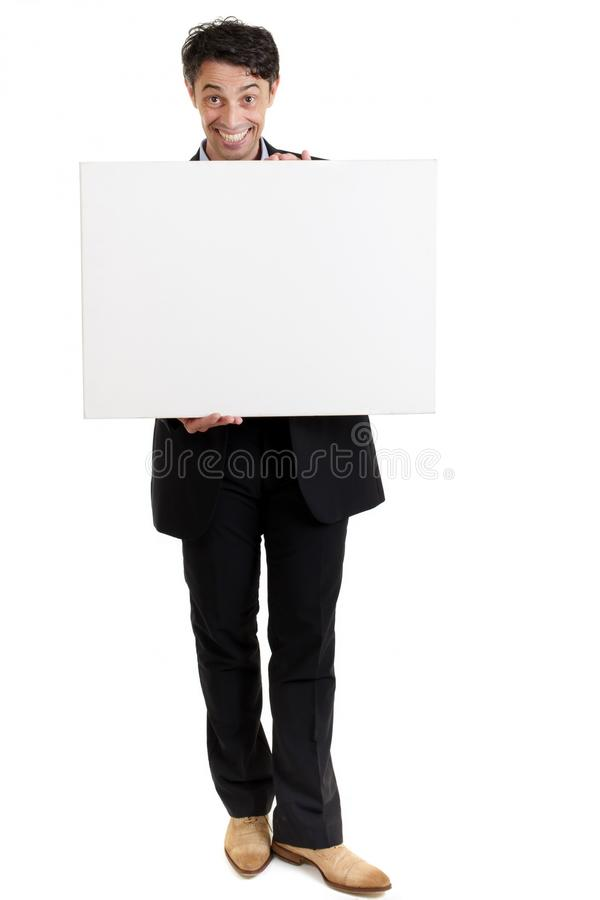 Persuasive man with a big smile and a blank sign. Persuasive middle-aged man with a big smile holding a blank sign in front of his chest as he draws your royalty free stock photo