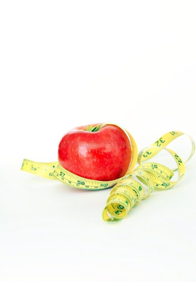 Perte de poids Bande de mesure enroulée autour d'une pomme photo libre de droits