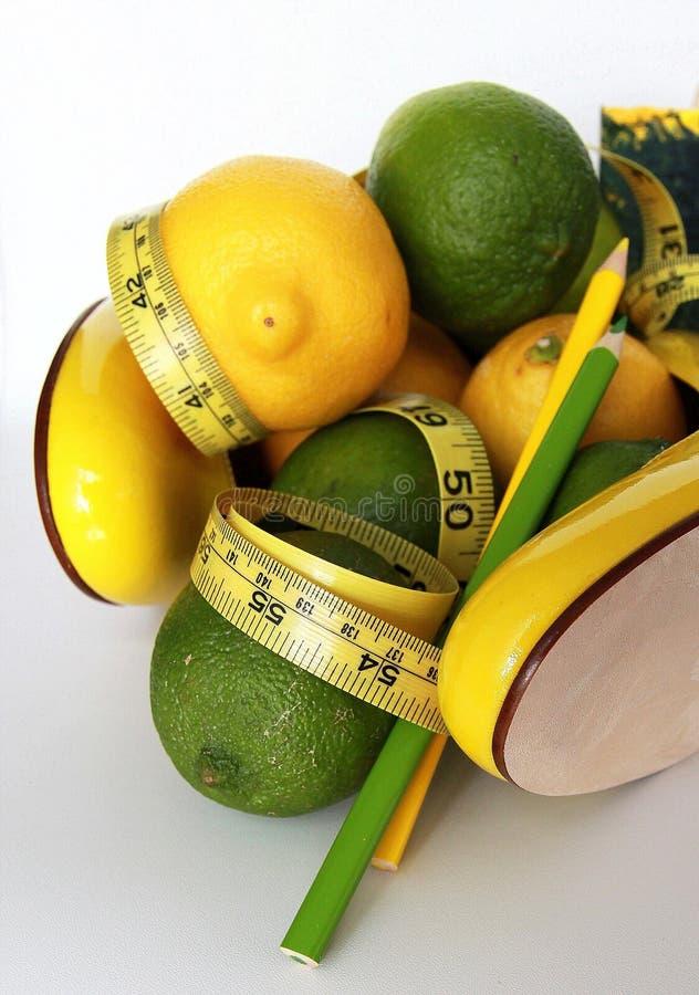Perte de poids Bande de mesure enroulée autour des citrons images stock