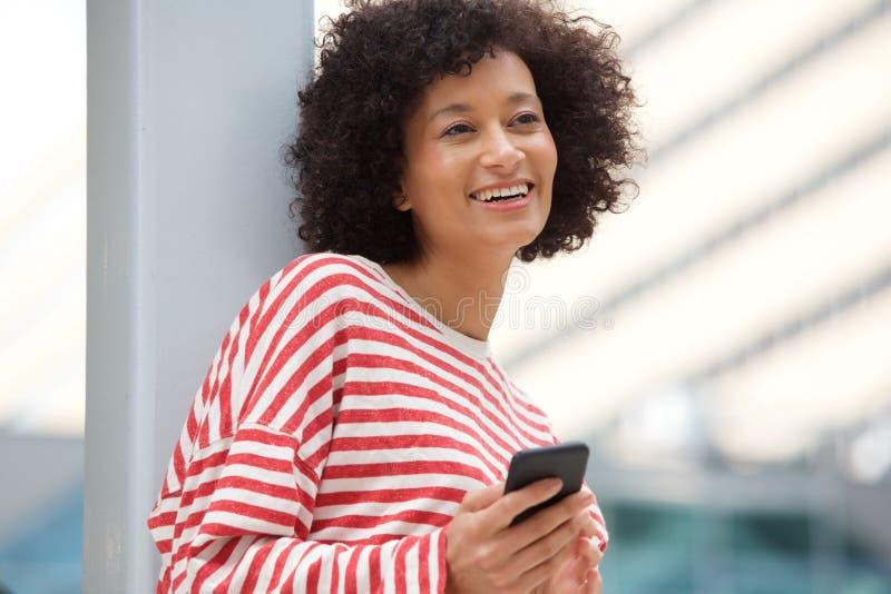 Perto acima da mulher afro-americano mais idosa que ri com telefone celular fora imagem de stock royalty free