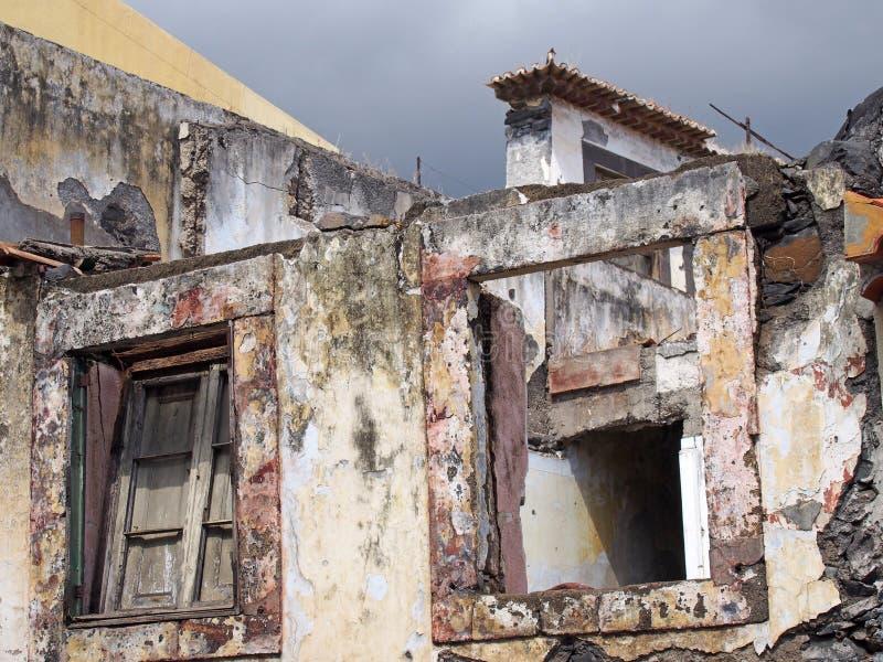 perto acima das janelas de uma casa sem telhado abandonada de desmoronamento com obturador quebrado e o c?u cinzento imagens de stock