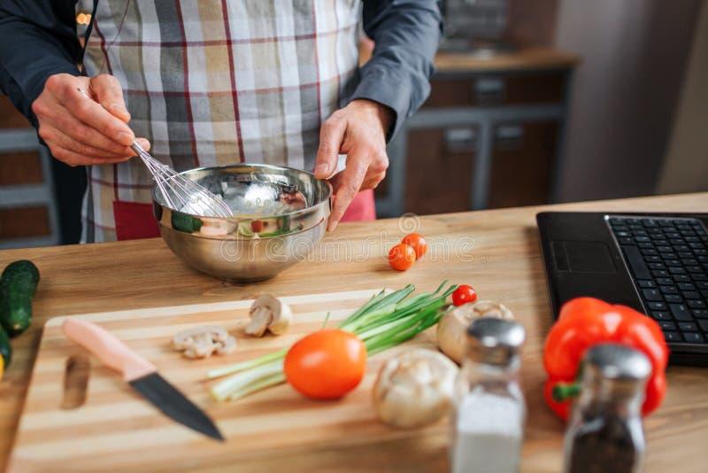 Perto acima das mãos do homem que misturam ovos na bacia Trabalha na tabela na cozinha Avental do desgaste do indivíduo Vegetais  foto de stock