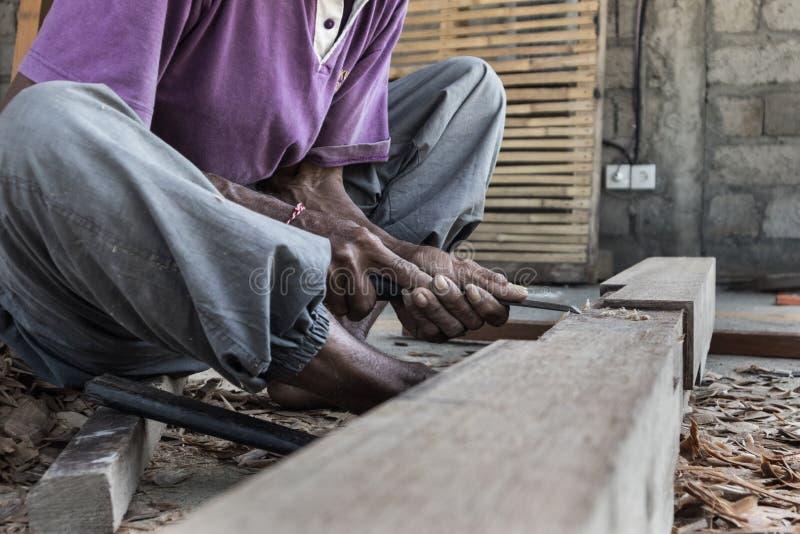 Perto acima de advirta as mãos do carpinteiro que trabalham na loja manual tradicional da carpintaria em um país do terceiro mund fotografia de stock