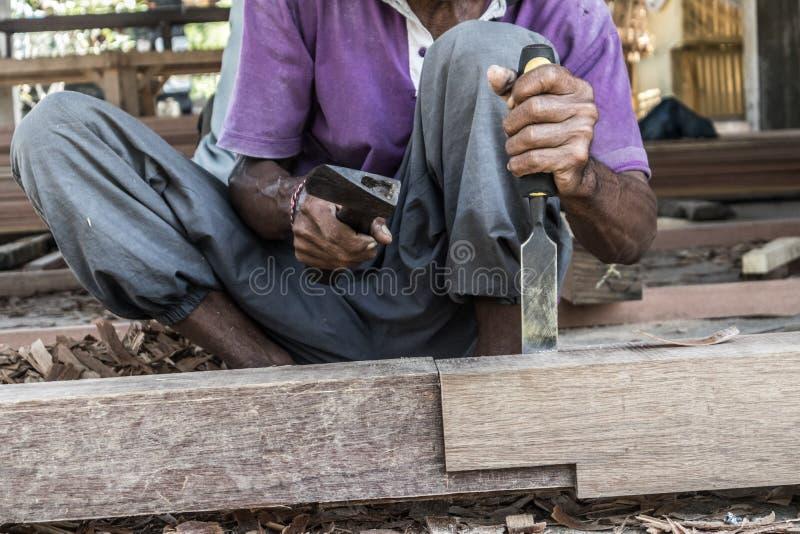 Perto acima de advirta as mãos do carpinteiro que trabalham na loja manual tradicional da carpintaria em um país do terceiro mund imagens de stock