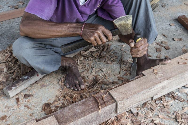 Perto acima de advirta as mãos do carpinteiro que trabalham na loja manual tradicional da carpintaria em um país do terceiro mund imagens de stock royalty free