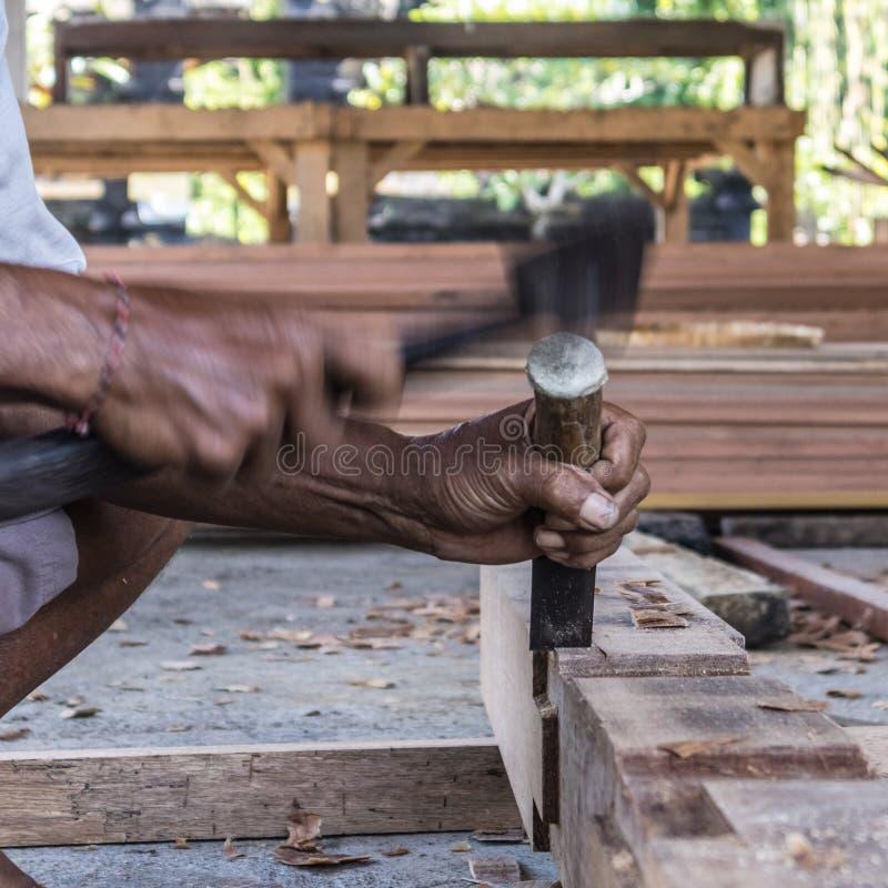 Perto acima de advirta as mãos do carpinteiro que trabalham na loja manual tradicional da carpintaria em um país do terceiro mund foto de stock royalty free