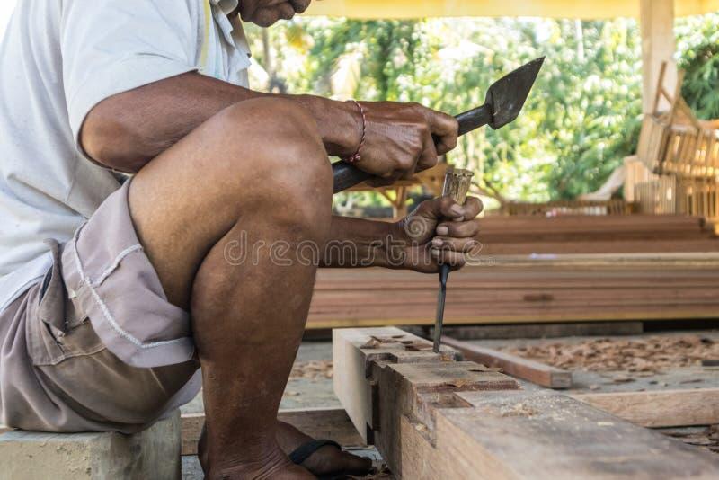 Perto acima de advirta as mãos do carpinteiro que trabalham na loja manual tradicional da carpintaria em um país do terceiro mund fotos de stock royalty free