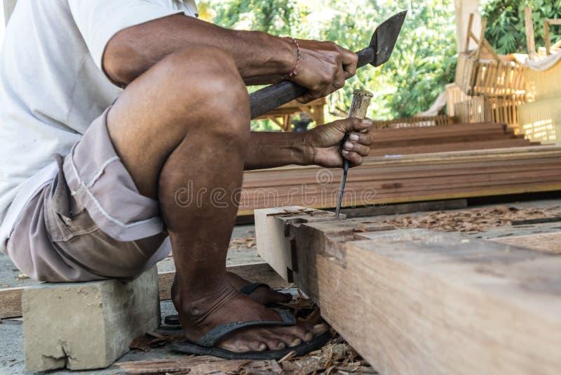 Perto acima de advirta as mãos do carpinteiro que trabalham na loja manual tradicional da carpintaria em um país do terceiro mund fotos de stock