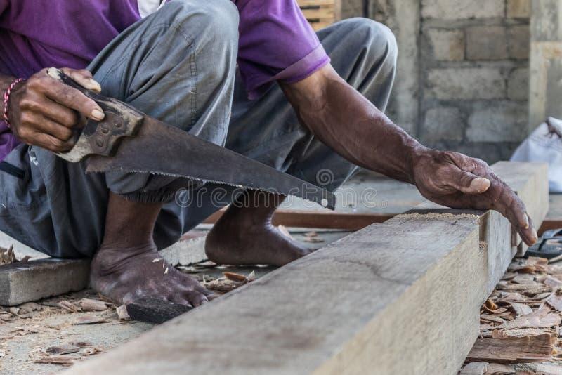 Perto acima de advirta as m?os do carpinteiro que trabalham na loja manual tradicional da carpintaria em um pa?s do terceiro mund imagem de stock