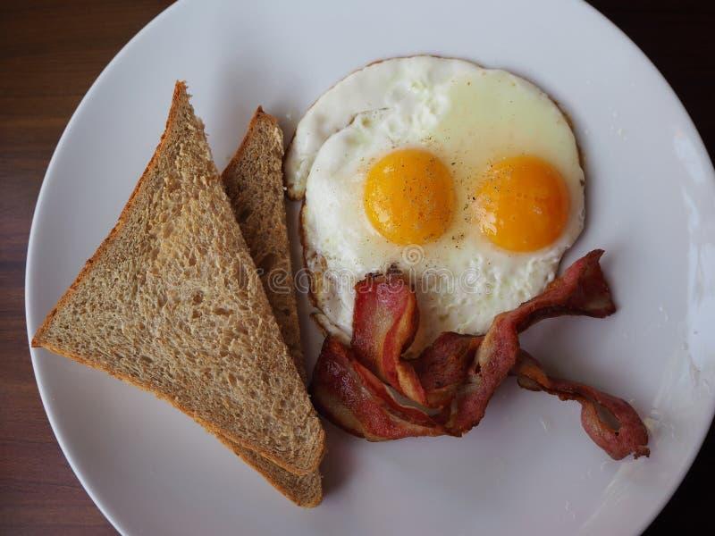 Perto acima de dois ovos fritos e pães com bacon Vista superior fotos de stock royalty free