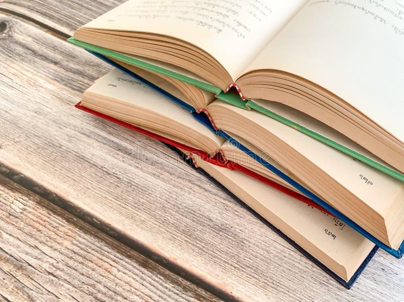 Perto acima de 4 novelas abertas e sobrepostas em uma tabela de madeira imagens de stock royalty free