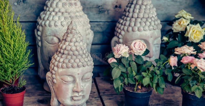 Perto acima de pedra poucas estátuas da cabeça de buddha entre flores nos potenciômetros no fundo de madeira Exterior, parque, de imagens de stock royalty free