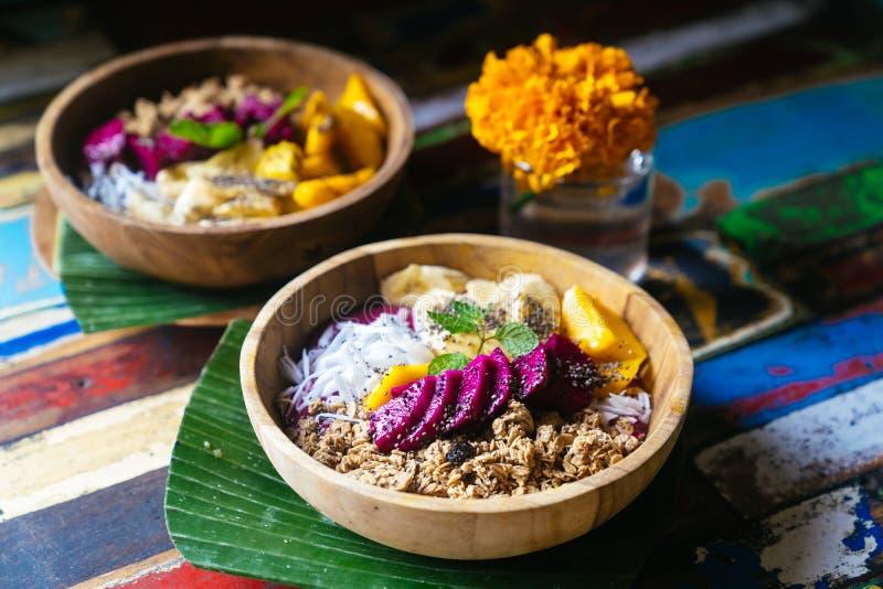 Perto acima de quatro bacias do batido feitas com manga, banana, granola, o coco raspado, o fruto do dragão, as sementes do chia  fotos de stock