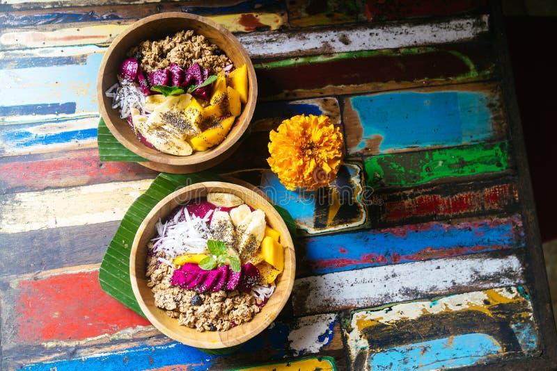 Perto acima de quatro bacias do batido feitas com manga, banana, granola, o coco raspado, o fruto do dragão, as sementes do chia  imagem de stock royalty free