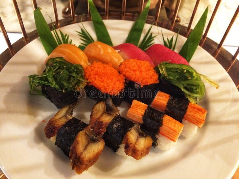 Perto acima de Shushi e de bufete do sashimi no jantar da noite resturant foto de stock