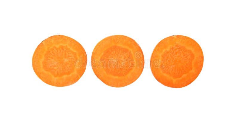 Perto acima de três fatias cortadas de cenoura sobre o branco fotografia de stock royalty free