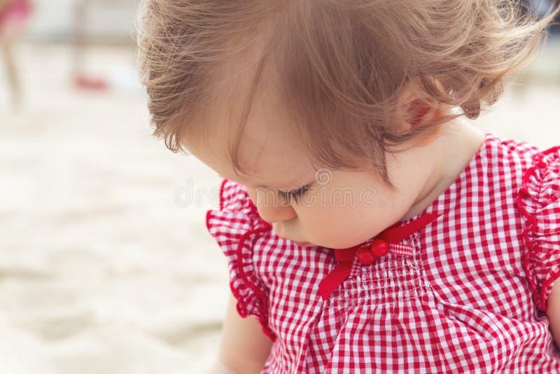Perto acima do bebê idoso de nove meses no fundo da praia Pouca consideravelmente criança infantil europeia bonito com cabelo esc imagem de stock