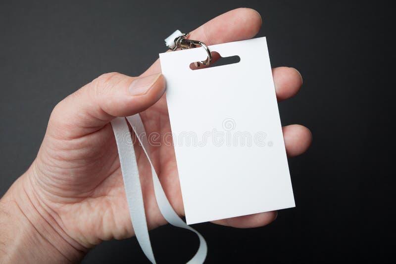Perto acima, mão que guarda o cartão plástico vazio branco da identificação da identificação, modelo imagens de stock royalty free