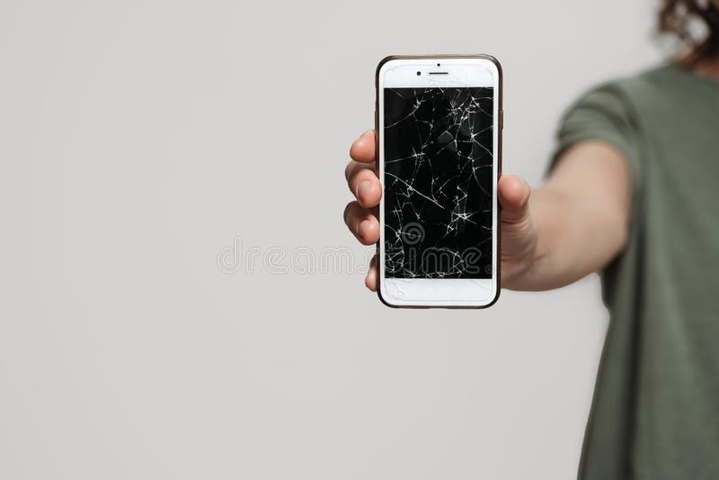 Perto acima, m?o que guarda smartphone quebrado com prote??o danificada da tela fotografia de stock