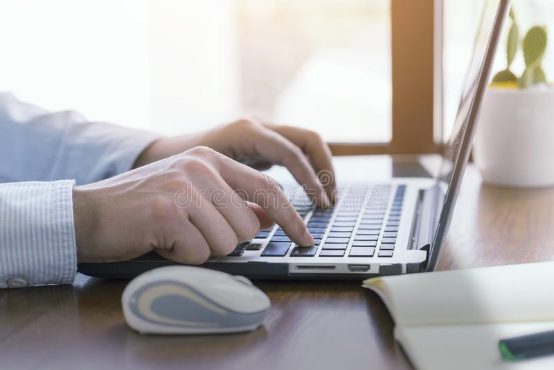 Perto acima, mãos do homem usando o portátil do computador, trabalhando fora imagem de stock