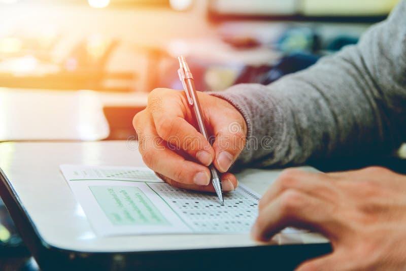 Perto acima, os exames do lápis da terra arrendada do estudante masculino de High School que escrevem na sala de aula para o test imagens de stock