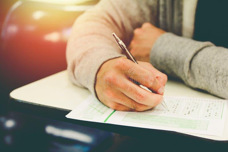 Perto acima, os exames do lápis da terra arrendada do estudante masculino de High School que escrevem na sala de aula para o test imagens de stock royalty free
