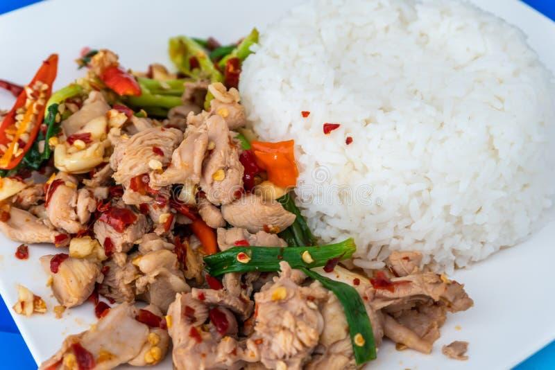Perto agite acima a galinha e a manjericão trituradas fritadas com arroz do jasmim na tabela É um alimento popular imagem de stock
