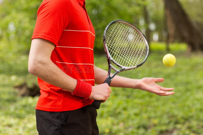Perto dos homens as m?os mant?m uma raquete e uma bola de t?nis no fundo verde Conceito do esporte imagem de stock
