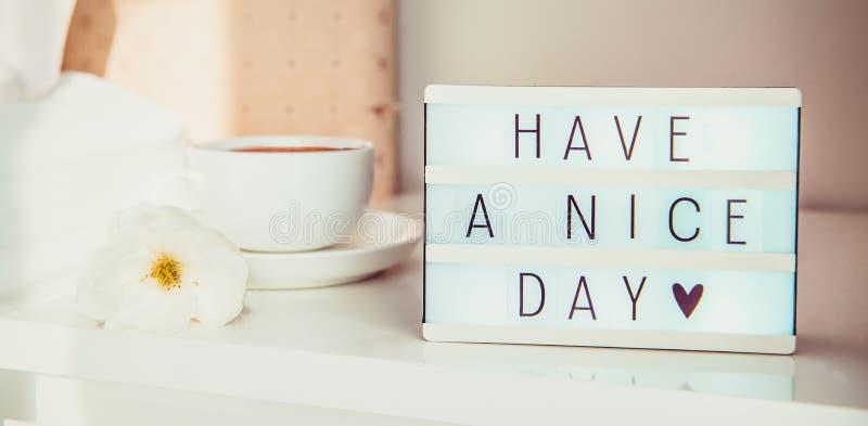 Perto tenha acima uma mensagem de texto do dia agradável na caixa leve, na xícara de café e na flor branca na tabela de cabeceira fotos de stock royalty free
