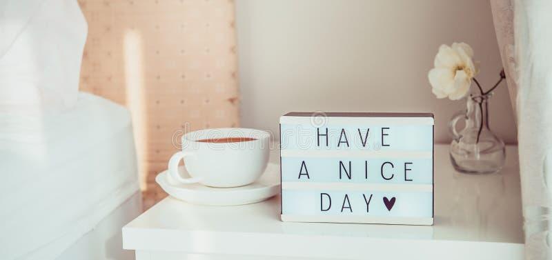 Perto tenha acima uma mensagem de texto do dia agradável na caixa leve, na xícara de café e na flor branca na tabela de cabeceira imagens de stock