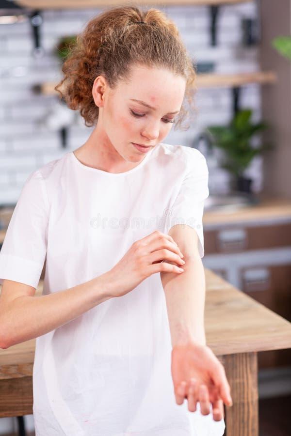 Perturbe a menina de cabelos compridos no t-shirt branco coberto em pontos vermelhos foto de stock